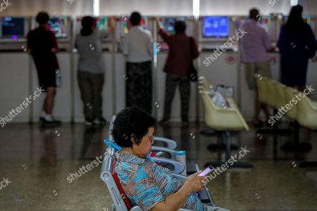 Chinese investors check stock prices at a brokerage house in Beijing, . Shares rose Thursday in Asia, tracking gains on Wall Street after Federal Reserve Chairman Jerome Powell suggested the U.S. central bank is ready to cut interest rates for the first time in a decade