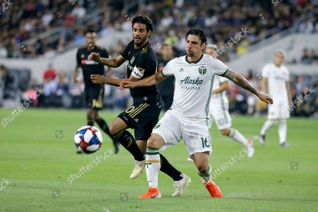 Los Angeles FC forward Carlos Vela, left, and Portland Timbers defender Zarek Valentin vie for the ball during the second half of a U.S. Open Cup quarterfinals soccer match in Los Angeles, . The Timbers won 1-0