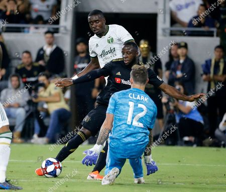 Los Angeles FC forward Adama Diomande, center, shoots against Portland Timbers goalkeeper Steve Clark (12) while defended by defender Larrys Mabiala during the second half of a U.S. Open Cup quarterfinals soccer match in Los Angeles, . The Timbers won 1-0