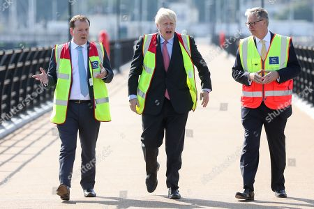 """Boris Johnson, former Britain foreign secretary, center, walks with Charlie Elphicke, Britain lawmaker, (L) and Doug Bannister, chief executive officer of Port of Dover Ltd., during a visit to the Port of Dover Ltd., as part of his Conservative Party leadership campaign tour, in Dover, Britain, 11 July 2019. Johnson, the overwhelming favorite to win, has pledged to lead Britain out of the European Union by the Oct. 31 deadline, """"do or die,"""" with or without a deal."""