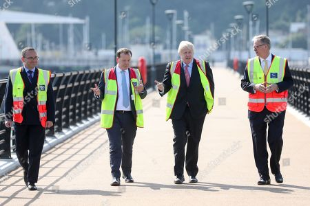 """Boris Johnson, former Britain foreign secretary, (2-R), walks with Charlie Elphicke, Britain lawmaker, (2-L) and Doug Bannister, chief executive officer of Port of Dover Ltd., (R) during a visit to the Port of Dover Ltd., as part of his Conservative Party leadership campaign tour, in Dover, Britain, 11 July 2019. Johnson, the overwhelming favorite to win, has pledged to lead Britain out of the European Union by the Oct. 31 deadline, """"do or die,"""" with or without a deal."""