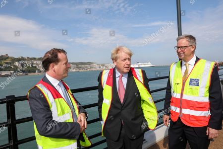 """Boris Johnson, former Britain foreign secretary, (C) speaks with Charlie Elphicke, Britain lawmaker, (L) and Doug Bannister, chief executive officer of Port of Dover Ltd., during a visit to the Port of Dover Ltd., as part of his Conservative Party leadership campaign tour, in Dover, Britain, 11 July 2019. Johnson, the overwhelming favorite to win, has pledged to lead Britain out of the European Union by the Oct. 31 deadline, """"do or die,"""" with or without a deal."""