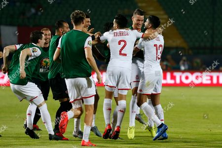 Tunisia's Ferjani Sassi, right, celebrates with his teammates after scoring during the African Cup of Nations quarterfinal soccer match between Madagascar and Tunisia in Al Salam stadium in Cairo, Egypt