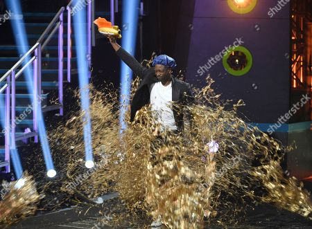 Stock Photo of Dwayne Wade holds up the legend award as he is covered in gold slime at the Kids' Choice Sports Awards, at the Barker Hangar in Santa Monica, Calif
