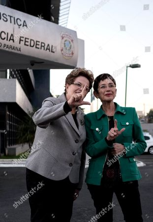 Spanish writer Pilar del Rio (R) and Brazilian former president Dilma Rousseff (L) form an L with their hands in reference to the Brazilian former president Luiz Inacio Lula da Silva after visiting him in jail at the headquarter of the Parana's state Federal Police in Curitiba, Brazil, 11 July 2019. Lula has been in prison since April of last year serving a sentence of 8 years and 10 months in prison for corruption and money laundering.