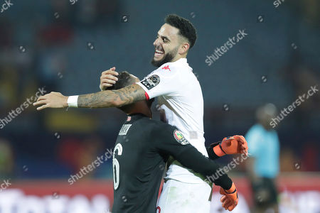 Stock Photo of Tunisia's Dylan Bronn, right, celebrates with Tunisia's goalkeeper Hassen Mouez end of the African Cup of Nations quarterfinal soccer match between Madagascar and Tunisia in Al Salam stadium in Cairo, Egypt