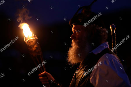Stock Image of Al Thompson, of Milan, Ind., waits to announce his clan's arrival during the opening torchlight service to begin the 64th annual Grandfather Mountain Highland Games at MacRae Meadows in Linville, N.C., . The games celebrate the history and culture of Scottish people in North Carolina