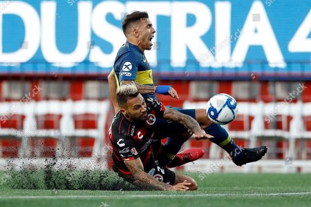 Tijuana's Julian Velazquez, below, collides with Boca Juniors's Carlos Tevez during the first half of a friendly soccer match, in Tijuana, Mexico
