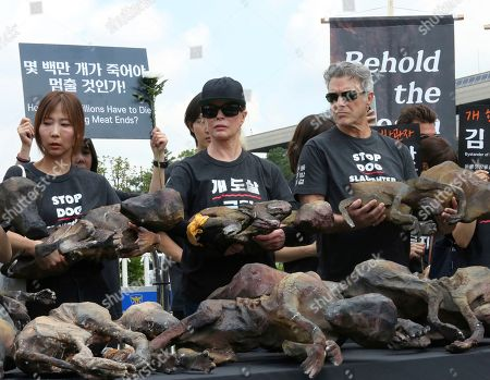 American actress Kim Basinger, center, holds a model of a slaughtered dog during a rally to oppose eating dog meat in front of the National Assembly in Seoul, South Korea, . July 12 is the day South Koreans eat healthy foods such as dog meat in the belief it would help them survive heat during summer