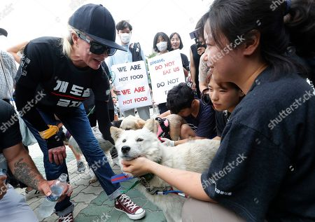 American actress Kim Basinger, left, watches a pet dog during a rally to oppose eating dog meat in front of the National Assembly in Seoul, South Korea, . July 12 is the day South Koreans eat healthy foods such as dog meat in the belief it would help them survive heat during summer