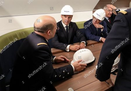 French President Emmanuel Macron (C) and former French Prime Minister Bernard Cazeneuve (2-R) listen in the living area as they visit the new French nuclear submarine 'Suffren' in Cherbourg, north-western France on July 12, 2019, as part of its official launch ceremony. The 99-metre-long black steel monster is named after Pierre-Andre Suffren, an admiral who distinguished himself against the English in the 18th century. The actual launch will only take place at the end of July, with a three-year delay, before dockside tests, then at sea, and its delivery to the French Navy in Toulon before summer 2020.