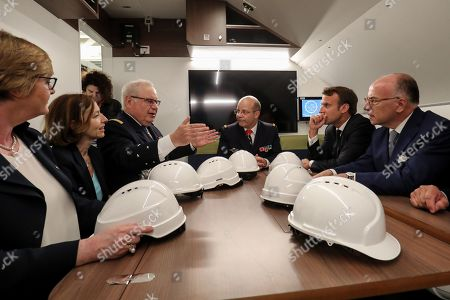 French President Emmanuel Macron (2R), former French Prime Minister Bernard Cazeneuve (R) and French Defence Minister Florence Parly (2L) listen in the living area as they visit the new French nuclear submarine 'Suffren' in Cherbourg, north-western France on July 12, 2019, as part of its official launch ceremony. The 99-metre-long black steel monster is named after Pierre-Andre Suffren, an admiral who distinguished himself against the English in the 18th century. The actual launch will only take place at the end of July, with a three-year delay, before dockside tests, then at sea, and its delivery to the French Navy in Toulon before summer 2020.