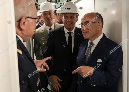 French President Emmanuel Macron (2R) and former French Prime Minister Bernard Cazeneuve (R) visit the new French nuclear submarine 'Suffren' in Cherbourg, north-western France on July 12, 2019, as part of its official launch ceremony. The 99-metre-long black steel monster is named after Pierre-Andre Suffren, an admiral who distinguished himself against the English in the 18th century. The actual launch will only take place at the end of July, with a three-year delay, before dockside tests, then at sea, and its delivery to the French Navy in Toulon before summer 2020.