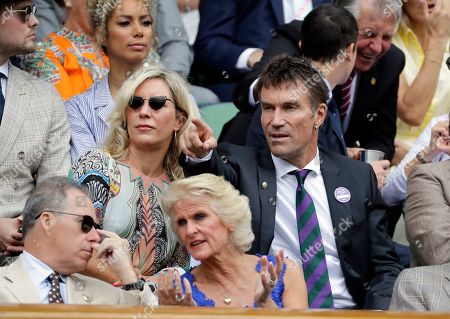 Former Wimbledon tennis champion Pat Cash, right, gestures as he sits in the Royal Box on Centre Court to watch a Men's singles semifinal match on day eleven of the Wimbledon Tennis Championships in London