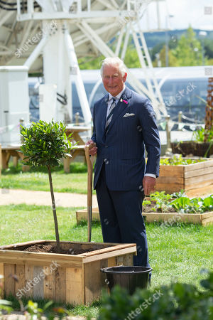 Prince Charles planting a tree and touring the GCHQ Garden.
