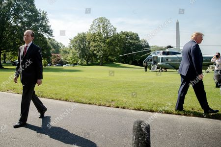 Donald Trump, Alex Acosta. Labor Secretary Alex Acosta, left, walks back into the White House as President Donald Trump, right, speaks to members of the media on the South Lawn in Washington, before Trump boards Marine One for a short trip to Andrews Air Force Base, Md. and then on to Wisconsin and Ohio