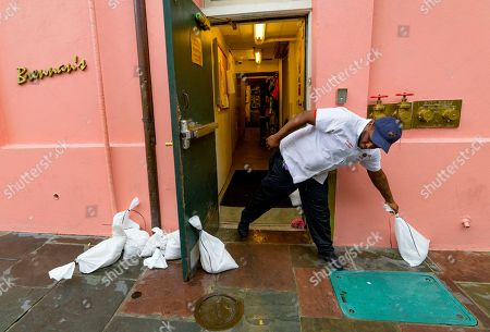 Chris John with Brennan's restaurant in the French Quarter moves sandbags as bands of rain from Tropical Storm Barry from the Gulf of Mexico move into New Orleans, La