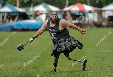 Matthew Hall, of Roanoke, Va., warms up before the weight toss event during the 64th Annual Grandfather Mountain Highland Games at MacRae Meadows in Linville, N.C., . The games celebrate the history and culture of Scottish people