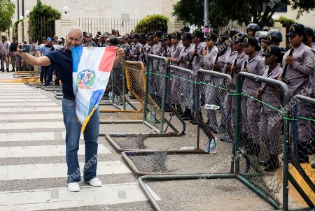 A protester, holding a national flag, poses for a selfie in front of a cordon of police blocking access to the National Congress during a protest against a constitutional reform that would allow President Danilo Medina a third term in office, in Santo Domingo, Dominican Republic . The amendment would let Medina stay in office until 2024 if re-elected and could be introduced in upcoming days, with legislators saying they are finalizing the proposal