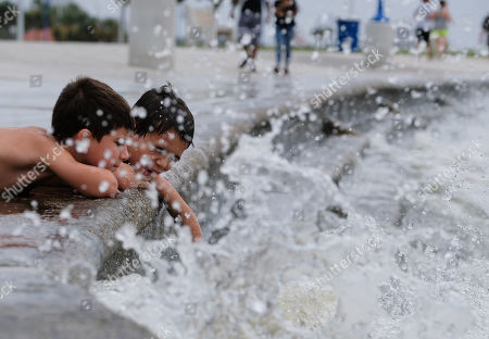 (front to back) Friends Landry Naccari, 8, and Rivers Gleason (son of former New Orleans Saints player Steve Gleason), 7, get splashed by the waters of Lake Pontchartrain as Tropical Storm Barry approaches in New Orleans, Louisiana, USA, on 12 July 2019. Tropical Storm Barry is predicted to make landfall as a Category 1 hurricane.