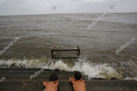(left to right) Friends Rivers Gleason (son of former New Orleans Saints player Steve Gleason), 7,  and Landry Naccari, 8, get splashed by the waters of Lake Pontchartrain as Tropical Storm Barry approaches in New Orleans, Louisiana, USA, on 12 July 2019. Tropical Storm Barry is predicted to make landfall as a Category 1 hurricane.