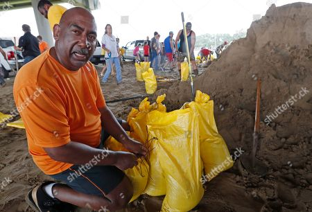 """Alfred Bartholomew of the Bayou Vista community, takes a break from helping Morgan City, La., residents fill sandbags for home barriers, . """"I came here with my truck to help my family, and then started helping others fill bags,"""" he said. """"Isn't that what we are supposed to do, help our fellow man"""