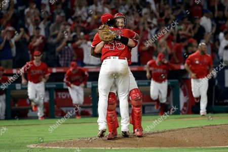 Felix Pena, Dustin Garneau. Los Angeles Angels relief pitcher Felix Pena, back to camera, celebrates with catcher Dustin Garneau after Pena and Taylor Cole threw a combined no-hitter against the Seattle Mariners during a baseball game, in Anaheim, Calif