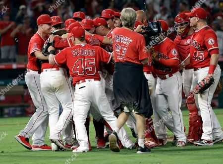 Los Angeles Angels relief pitcher Felix Pena, second from left, is congratulated by teammates after he finished off a combined no-hitter against the Seattle Mariners during a baseball game, in Anaheim, Calif. Taylor Cole pitched the first two innings