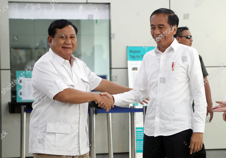 Indonesian President Joko Widodo (R) shakes hands with Indonesian presidential candidate Prabowo Subianto (L) wave during their meeting on a train in Jakarta, Indonesia, 13 July 2019. Jokowi and Prabowo meet after Indonesia's Constitutional judge rejected the claims of candidate Prabowo's legal team in court to challenge the results of the presidential election.