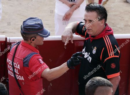 US actor, film director and producer Daniel Baldwin (R) chats with a policeman at the bullring at the end of the seventh 'encierro', or running-with-the-bulls, of the Sanfermines festivities in Pamplona, Spain, 13 July 2019. The festival of San Fermin, locally known as Sanfermines, is held annually from 06 to 14 July in commemoration of the city's patron saint. Hundreds of thousands of visitors from all over the world attend the fiesta. Many of them physically participate in the highlight event - the running of the bulls, or encierro - where they attempt to outrun the bulls along a route through the narrow streets of Pamplona's old city.