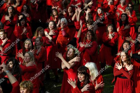 Stock Image of Kate Bush fans dressed in red dance as they recreate her film clip from the song 'Wuthering Heights' during The Most Wuthering Heights Day Ever flash mob at Edinburgh Gardens in Melbourne, Australia, 13 July 2019. Annually a group of Kate Bush fans re-enact the choerography of the singer's famous song 'Wuthering Heigths'.