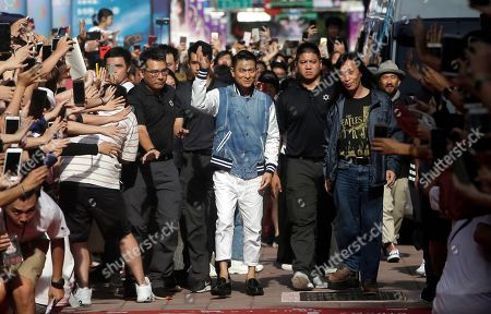 "Hong Kong actor Andy Lau, center, waves as he arrives with director Herman Yau, right, for a media event to promote their new movie ""The White Storm 2 - Drug Lords"" in Taipei, Taiwan"