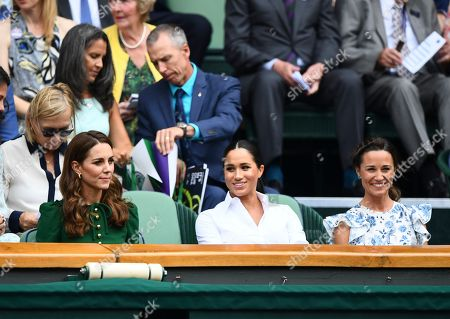 Stock Picture of Catherine Duchess of Cambridge looks on as Meghan Duchess of Sussex and Pippa Middleton smile in the Royal Box on Centre Court
