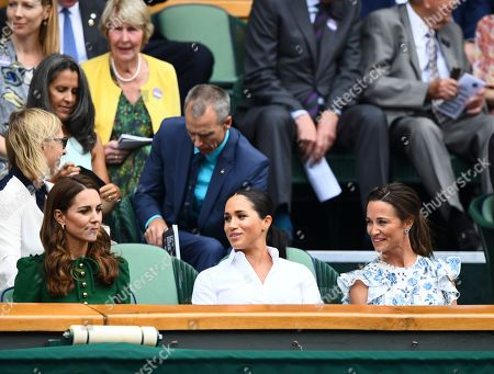 Catherine Duchess of Cambridge looks on as Meghan Duchess of Sussex and Pippa Middleton turn to her in the Royal Box on Centre Court