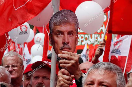 Communist Party of the Russian Federation activist holds a portrait of agriculture farm Sovkhoz Imeni Lenina's Director Pavel Grudinin during a rally 'For justice and the rights of citizens! Stop the arbitrariness of power! Defending Grudinina!' on the Revolution Square in Moscow, Russia, 13 July 2019. The participants demand to stop the arbitrariness in relation to the Sovkhoz Imeni Lenina Director, former Russian presidential candidate of the Communist Party, Pavel Grudinin.