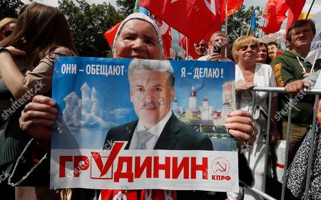 Stock Image of Communist Party of the Russian Federation activist holds a placard of agriculture farm Sovkhoz Imeni Lenina's Director Pavel Grudinin during a rally 'For justice and the rights of citizens! Stop the arbitrariness of power! Defending Grudinina!' on the Revolution Square in Moscow, Russia, 13 July 2019. The participants demand to stop the arbitrariness in relation to the Sovkhoz Imeni Lenina Director, former Russian presidential candidate of the Communist Party, Pavel Grudinin.
