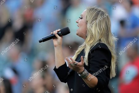 Stock Image of Country singer Clare Dunn sings the national anthem prior to a baseball game between the Baltimore Orioles and the Tampa Bay Rays, in Baltimore