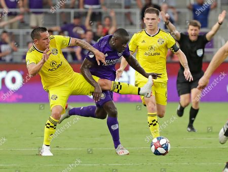 Columbus Crew's David Guzman, left, tries to move the ball past Orlando City's Benji Michel as Will Trapp, right, watches during the first half of an MLS soccer match, in Orlando, Fla