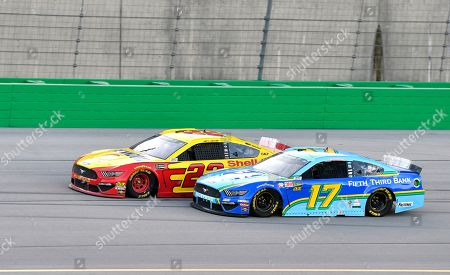 Joey Logano (22) tries to hold off Ricky Stenhouse Jr. (17) during the NASCAR Cup Series auto race at Kentucky Speedway in Sparta, Ky