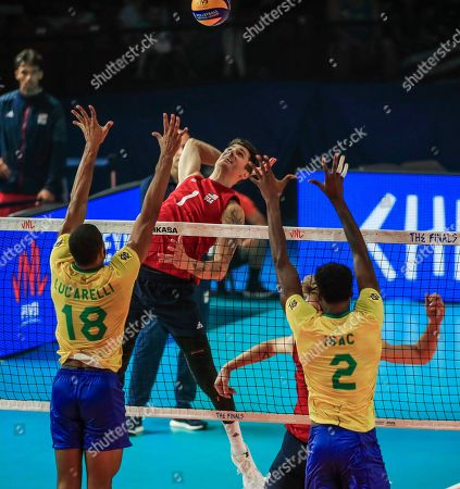 Stock Image of USA's Matthew Anderson (C) in action against Brazil's Ricardo Lucarelli Souza(L) and Brazil's Isac Santos (R) during the FIVB Volleyball Men's Nations League semifinal match between Brazil and the USA at Credit Union 1 Arena in Chicago, Illinois, USA, 13 July 2019. Russia defeated Poland to reach the finals.