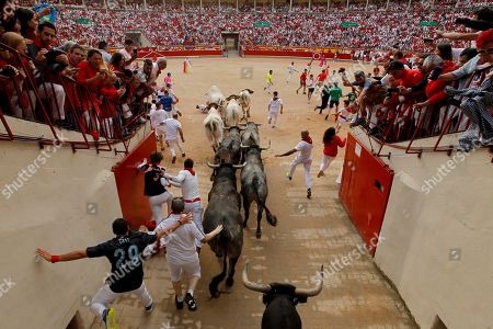 "Revellers and fighting bulls arrive at the bullring during the running of the bulls at the San Fermin Festival, in Pamplona, northern Spain, . The San Fermin fiesta made internationally famous by Ernest Hemingway in his novel ""The Sun Also Rises"" draws around 1 million partygoers each year"