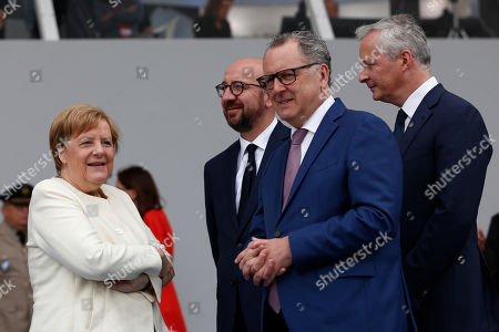German Chancellor Angela Merkel, left, Belgium Prime Minister Charles Michel, French House speaker Richard Ferrand and French Economy Minister Bruno Le Maire wait for the start of the Bastille Day parade on the Champs Elysees avenue in Paris