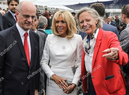 French wife's president Brigitte Macron (C) talks with French Education and Youth Affairs Minister Jean-Michel Blanquer, left, and French Junior Minister for Disability Issues Sophie Cluzel chat after the annual Bastille Day military parade on the Champs-Elysees in Paris