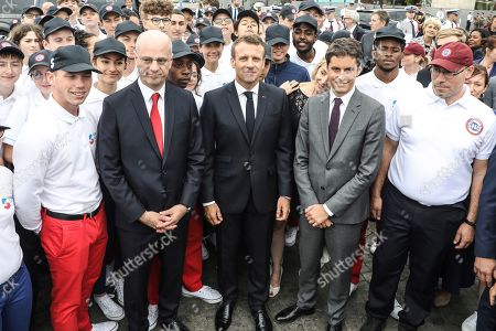 French President Emmanuel Macron, center, poses French Junior Minister for Education Gabriel Attal, center right, and French Education and Youth Affairs Minister Jean-Michel Blanquer, left, and with members of the civic service and the universal national service SNU (Service National Universel) after the annual Bastille Day military parade on the Champs-Elysees in Paris