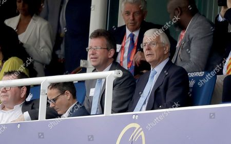 Britain's former Prime Minister John Major, right, sits with Britain's Secretary of State for Digital, Culture, Media and Sport Jeremy Wright, left, during the Cricket World Cup final match between England and New Zealand at Lord's cricket ground in London