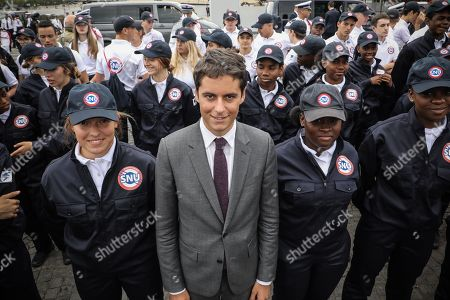 French Junior Minister for Education Gabriel Attal (C) poses with members of the civic service and the universal national service SNU (Service National Universel) at the end of the annual Bastille Day military parade down the Champs Elysees avenue in Paris, France, 14 July 2019. Bastille Day, the French National Day, is held annually on 14 July to commemorate the storming of the Bastille fortress in 1789.