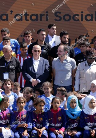 Stock Photo of Javier Tebas, President of La Liga Foundation (C-L) and Jordan's Prince Ali Bin Al-Hussein, founder of  the AFDP (Asian Football Development Project) (C-R) pose for a photograph during a celebration of La Liga socio-educational project, at the Big Sports House Stadium, in the Zaatari refugee camp, about 100 km north of Amman, Jordan, 14 July 2019. Zaatari refugee camp is only 10 km away from the Syrian border and houses some 80000 refugees, fifty per cent of whom are under the age of 18. The Zaatari socio-educational project was developed by La Liga in collaboration with the AFDP (Asian Football Development Project), it involves some 33 clubs of the Spanish League and aims to develop various projects favorable to coexistence, integration and adaptation of the participants and their families.