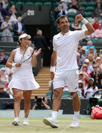 Stock Photo of Taiwan's Latisha Chan, left, and Croatia's Ivan Dodig celebrate defeating Latvia's Jelena Ostapenko and Sweden's Robert Lindstedt during the mixed doubles final match of the Wimbledon Tennis Championships in London