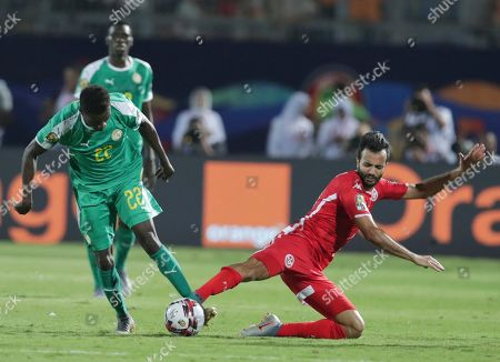 Senegal's Moussa Wague, left, and Tunisia's Taha Khenissi fight for the ball during the African Cup of Nations semifinal soccer match between Senegal and Tunisia in 30 June stadium in Cairo, Egypt
