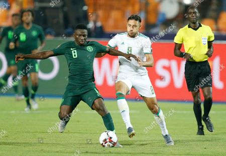 Nigeria's Oghenekaro Etebo, left, and Algeria's Mohamed Belaili fight for the ball during the African Cup of Nations semifinal soccer match between Algeria and Nigeria in Cairo International stadium in Cairo, Egypt